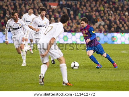 BARCELONA - JANUARY 25: Leo Messi (R) in action during the Spanish Cup match between FC Barcelona and Real Madrid, final score 2 - 2, on January 25, 2012, in Barcelona, Spain. - stock photo