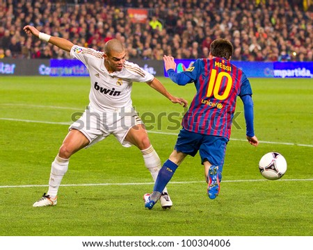BARCELONA - JANUARY 25: Pepe Laveran (L) and Leo Messi in action during the Spanish Cup match between FC Barcelona and Real Madrid, final score 2 - 2, on January 25, 2012, in Barcelona, Spain. - stock photo