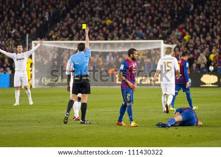 BARCELONA - JANUARY 25: Referee giving yellow card to Sergio Ramos during the Spanish Cup match between FC Barcelona and Real Madrid, final score 2 - 2, on January 25, 2012, in Barcelona, Spain. - stock photo