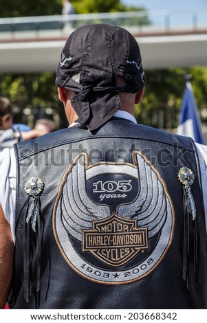 BARCELONA - JULY 05, 2014: Unidentified person with typical biker jacket a Harley Davidson motorbike at an exhibition during BARCELONA HARLEY DAYS 2014. Distinctive groups and related associations. - stock photo