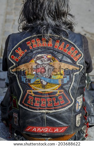 BARCELONA - JULY 06, 2014: Unidentified person with typical biker jacket a Harley Davidson motorbike at an exhibition during BARCELONA HARLEY DAYS 2014. Distinctive groups and related associations. - stock photo