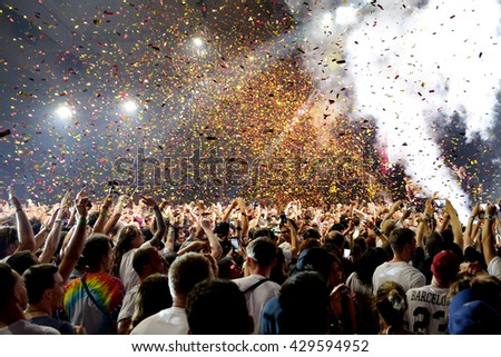 BARCELONA - JUN 19: Crowd in a concert, while throwing confetti from the stage at Sonar Festival on June 19, 2015 in Barcelona, Spain. - stock photo