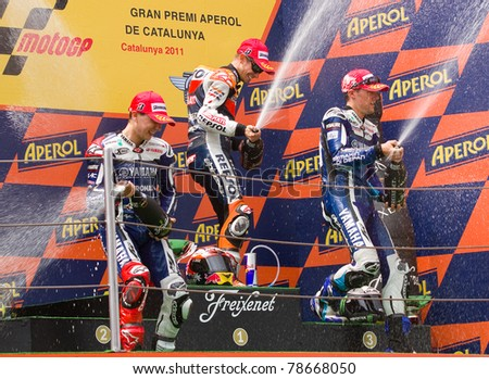 BARCELONA - JUNE 5: Casey Stoner (1st), Jorge Lorenzo (2nd) and Ben Spies (3dr) celebrating their trophies in the podium after the MotoGP Grand Prix of Catalunya, on June 5, 2011 in Barcelona, Spain. - stock photo