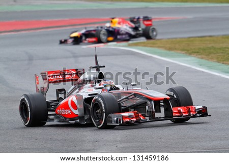 BARCELONA - MARCH 1: Jenson Button of Vodafone McLaren Mercedes F1 team leads Sebastian Vettel in Red Bull at Formula One Test Days at Catalunya circuit on March 1, 2013 in Barcelona, Spain.