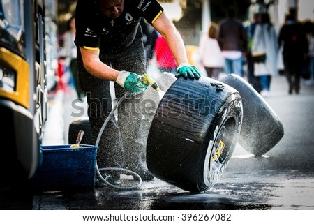BARCELONA - MARCH 2: Mechanic of Renault F1 Team washes tires at Formula One Test Days at Catalunya circuit on March 2, 2016 in Barcelona, Spain. - stock photo