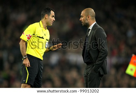 BARCELONA - MARCH 3: Referee Velasco Carballo talks with Pep Guardiola of Barcelona during the Spanish league match against Sporting Gijon at the Camp Nou stadium on March 3, 2012 in Barcelona, Spain - stock photo