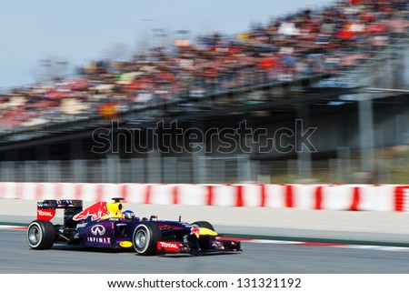 BARCELONA - MARCH 3: Sebastian Vettel of Infiniti Red Bull Racing F1 team passes grandstand with spectators at Formula One Test Days at Catalunya circuit on March 3, 2013 in Barcelona, Spain. - stock photo