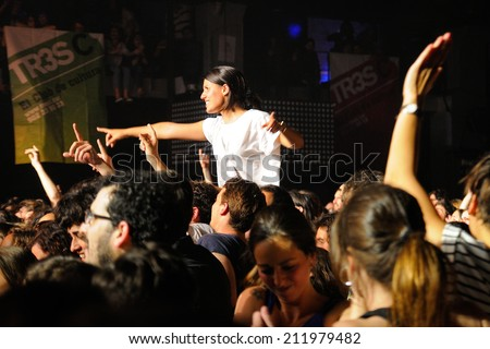 BARCELONA - MAY 16: A girl stands over the crowd in a concert at Razzmatazz discotheque on May 16, 2014 in Barcelona, Spain. - stock photo
