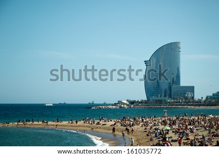 BARCELONA - MAY 3: city beach, 400 meters long, it one of 10 best urban beaches of the world. Tourists rest along Barceloneta beach, May 03, 2013 in Barcelona, Spain - stock photo