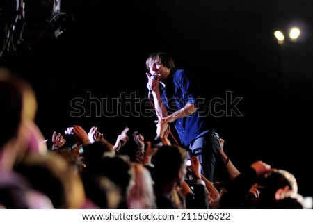BARCELONA - MAY 23: Frontman of Phoenix (band) singing surrounded by the audience performs at Heineken Primavera Sound 2013 Festival on May 23, 2013 in Barcelona, Spain.