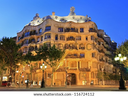BARCELONA-MAY 31: La Pedrera or Casa Mila at dusk, built during the years 1905-1910 and designed by Antoni Gaudi, with traffic lights, on May 31, 2012, Barcelona, Spain. - stock photo
