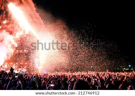 BARCELONA - MAY 29: People watching a concert by the famous band Arcade Fire, while throwing confetti from the stage at Heineken Primavera Sound 2014 Festival on May 29, 2014 in Barcelona, Spain. - stock photo
