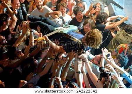 BARCELONA - MAY 30: The guitar player of Ty Segall (band) performs above the spectators (crowd surfing or mosh pit) at Heineken Primavera Sound 2014 Festival on May 30, 2014 in Barcelona, Spain. - stock photo