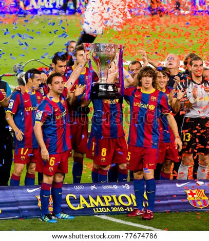 BARCELONA - MAY 15: Xavi Hernandez and Carles Puyol holds the Spanish League Championship Trophy in Camp Nou stadium, on May 15, 2011 in Barcelona, Spain. - stock photo