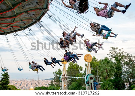 BARCELONA - SEP 5: People have fun at the carousel flying swing ride attraction at Tibidabo Amusement Park on September 5, 2015 in Barcelona, Spain. - stock photo