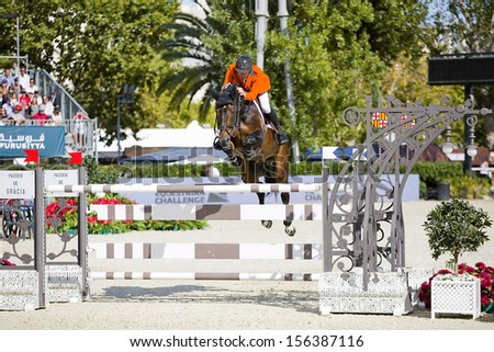 BARCELONA - SEPTEMBER 29: Jur Vrieling from Netherlands jumps a horse jumping obstacle at CSIO - Furusiyya FEI Nations Cup Horse Jumping Final Competition, on September 29, 2013, in Barcelona, Spain.