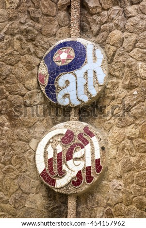 BARCELONA, SPAIN - APRIL 28, 2015: An emblem for Park Guell formed out of ceramic tiles as seen on an exterior wall that surrounds the park. The park was designed by Antoni Gaudi. - stock photo