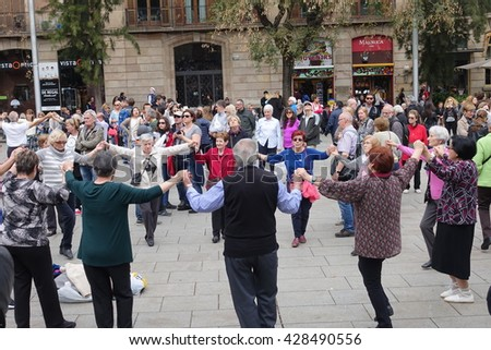 Barcelona, Spain - April 10, 2016:People dancing national dance Sardana holding hands in front of The Cathedral of the Holy Cross in Gothic Quarter of Barcelona in Spain