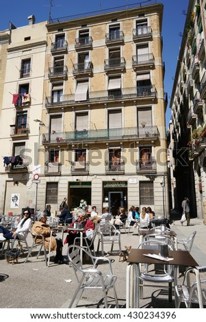 Barcelona, Spain - April 07, 2016:People sitting sidewalk cafe on April 07, 2016. El Born is a trendy area in Barcelona that has become a major tourist attraction.