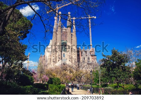 BARCELONA, SPAIN - APRIL 8, 2013: Sagrada Familia Cathedral behind the trees. Impressive Cathedral designed by Antoni Gaudi in Gothic Style is under construction. UNESCO World Heritage Site - stock photo