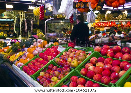 BARCELONA, SPAIN - APRIL 27: Tourists shop in famous La Boqueria market on April 27, 2012 in Barcelona, Spain.One of the oldest markets in Europe that still exist. Established 1217. - stock photo