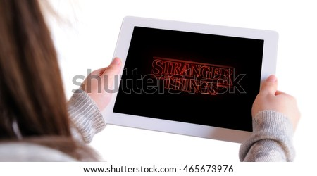 BARCELONA, SPAIN - AUG 8, 2016: Unrecognizable woman watching Stranger Things, a science fiction horror web television series released on Netflix, on an Apple Ipad, isolated on white background.