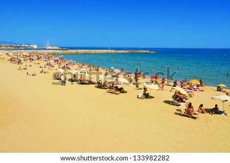 BARCELONA, SPAIN - AUGUST 16: Barceloneta Beach on August 16, 2011 in Barcelona, Spain. This beach, 422 meters long, hosts about 400,000 visitors during the summer season - stock photo