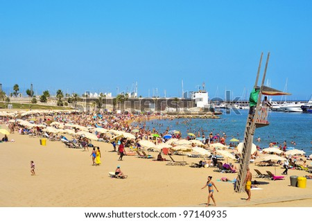 BARCELONA, SPAIN - AUGUST 8: Barceloneta-Somorrostro Beach on August 8, 2011 in Barcelona, Spain. This beach, 522 meters long, hosts about 400,000 visitors during the summer season - stock photo
