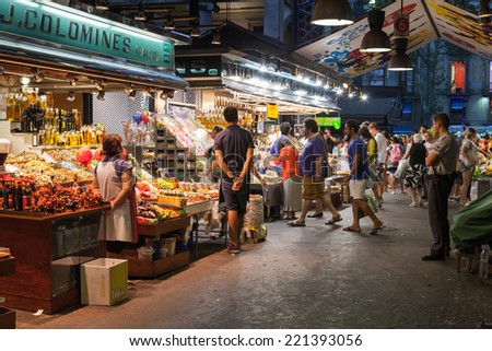 BARCELONA, SPAIN - AUGUST 25, 2014: buyers and sellers of La Boqueria, marketplace in old part of Barcelona - stock photo
