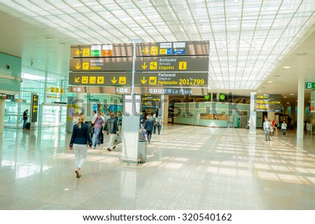 BARCELONA, SPAIN - 8 AUGUST, 2015: Inside arrivals terminal walking through building with signs and information around at airport.