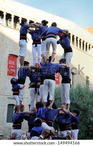 "BARCELONA, SPAIN - AUGUST 10: Unidentified people from team ""Castellers de la Vila de Gracia"" on August 10, 2013 in Barcelona. Catalan human towers are on UNESCO's list of Intangible Cultural Heritage"