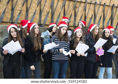 BARCELONA, SPAIN - DECEMBER 22, 2014: A group of young, singing Christmas carols in front of an entrance of La Sagrada Familia. - stock photo