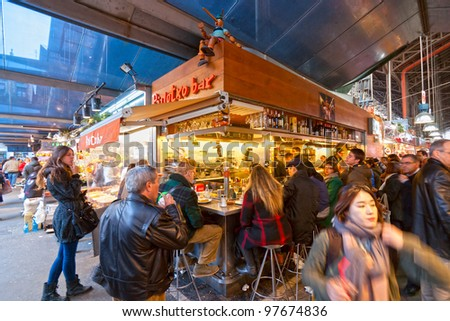 BARCELONA, SPAIN - DECEMBER 20: Tourists shop in famous La Boqueria market on December 20, 2011 in Barcelona, Spain. One of the oldest markets in Europe that still exist. Established 1217. - stock photo