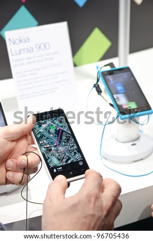 BARCELONA, SPAIN - FEB 26: Visitor of the GSMA MWC 2012 tests the new Nokia Lumia 900 at the Nokia exhibition stand on Feb 26, 2012 in Barcelona, Spain - stock photo