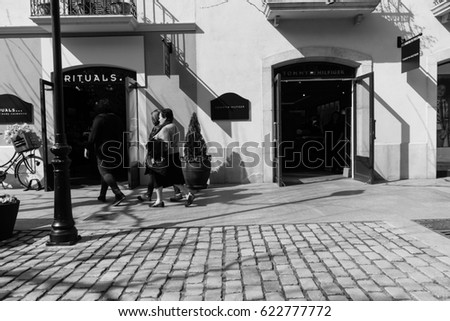 BARCELONA,SPAIN - February 27,2017: Shot of La Roca street  in Barcelona, Spain. This image may contain noise ,blurry clouds due to long exposure, soft focus and poor lighting.