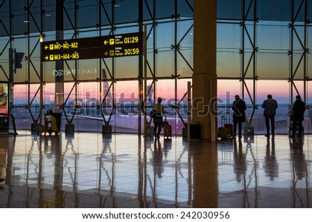 BARCELONA, SPAIN - JANUARY 05, 2015: Silhouette of passengers walking around the airport at dawn. El Prat airport in Barcelona