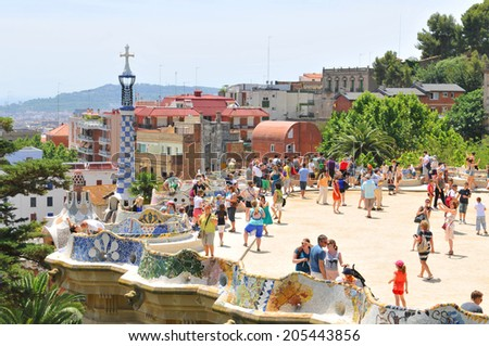 BARCELONA, SPAIN - JULY 08, 2012: Tourists visit the famous Park Guell, architectural landmark designed by the famous architect Antonio Gaudi