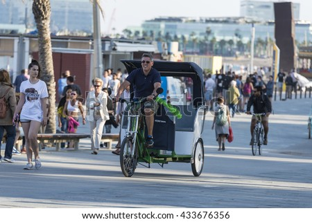Barcelona, Spain - June 1, 2016: Barcelona promenade full of people walking or playing sports. In the foreground a young man in a rickshaw tricycle