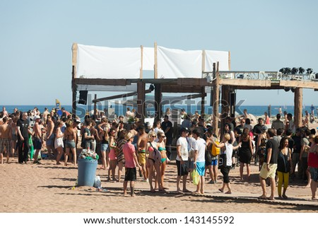 BARCELONA, SPAIN - JUNE 16: Open air party on Sant Adria beach in June 16, 2013 in Barcelona, Spain.  Mediterranean coast in Catalonia has beaches with entertainment to suit all tastes - stock photo