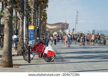 BARCELONA, SPAIN - JUNE1, 2014: People walking along Barceloneta Beach promenade with Frank Gehry's Peix d'Or (Whale Sculpture) in the background.