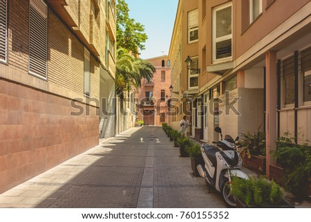 BARCELONA, SPAIN - June 20, 2017 : street atmosphere in a typical little street of barcelona where a woman walks