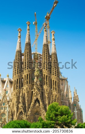BARCELONA, SPAIN - JUNE 12, 2014: The Basilica of La Sagrada Familia against blue sky. Designed by Antoni Gaudi, its construction began in 1882 and is not finished yet  - stock photo