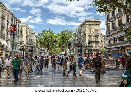 BARCELONA, SPAIN - JUNE 29,2014: Tourists walk famous Rambla street in Barcelona, Spain. According to Mastercard, Barcelona is the 15th most visited city worldwide (8.8m in 2013). - stock photo
