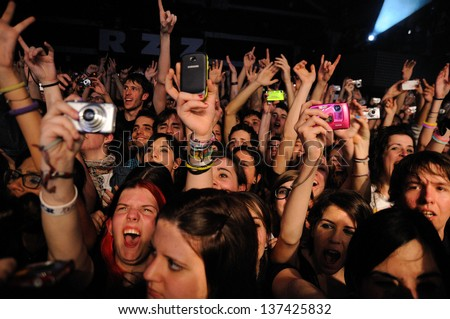 BARCELONA, SPAIN - MARCH 13: A large crowd of teenagers fans of Simple Plan band, screams at Razzmatazz on March 13, 2012 in Barcelona, Spain. - stock photo
