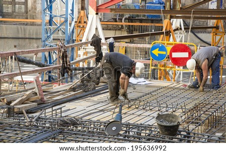 Barcelona, Spain - March 7, 2014: Construction workers are doing a floor for a luxury hotel in the old town. Construction workers are doing a floor with two road signs behind.