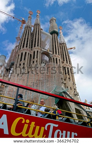 Barcelona, Spain - May 17, 2014: Cathedral of the Sagrada Familia inspect passengers tour bus. The spiers of the cathedral flock to the sky.