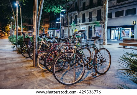 Barcelona, Spain - May 22, 2015: Locked bicycles on a pavement in Eixample district of Barcelona city