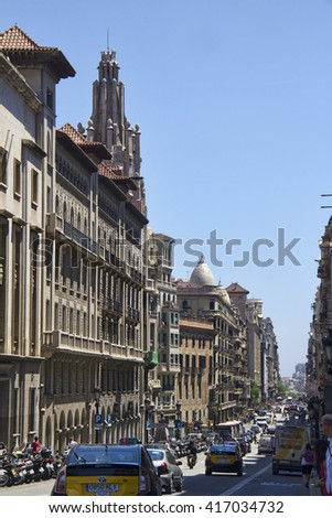 Barcelona, Spain - May 28, 2015: Taxi cabs and other traffic in a street with historical buildings in Barcelona, on May 28, 2015 in Barcelona, Spain - stock photo