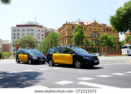 BARCELONA, SPAIN - MAY 27: The taxi cars and tourists enjoiying their vacation on May 27, 2015 in Barcelona, Spain. Up to 60 mln tourists is expected to visit Spain in year 2015. - stock photo