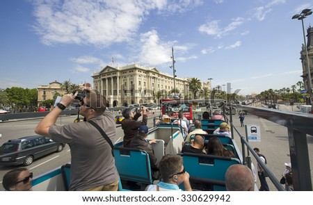 Barcelona, Spain - May 25, 2015: Tourists take pictures on a double decker bus touring around the city of Barcelona, Spain on May 25, 2015. - stock photo